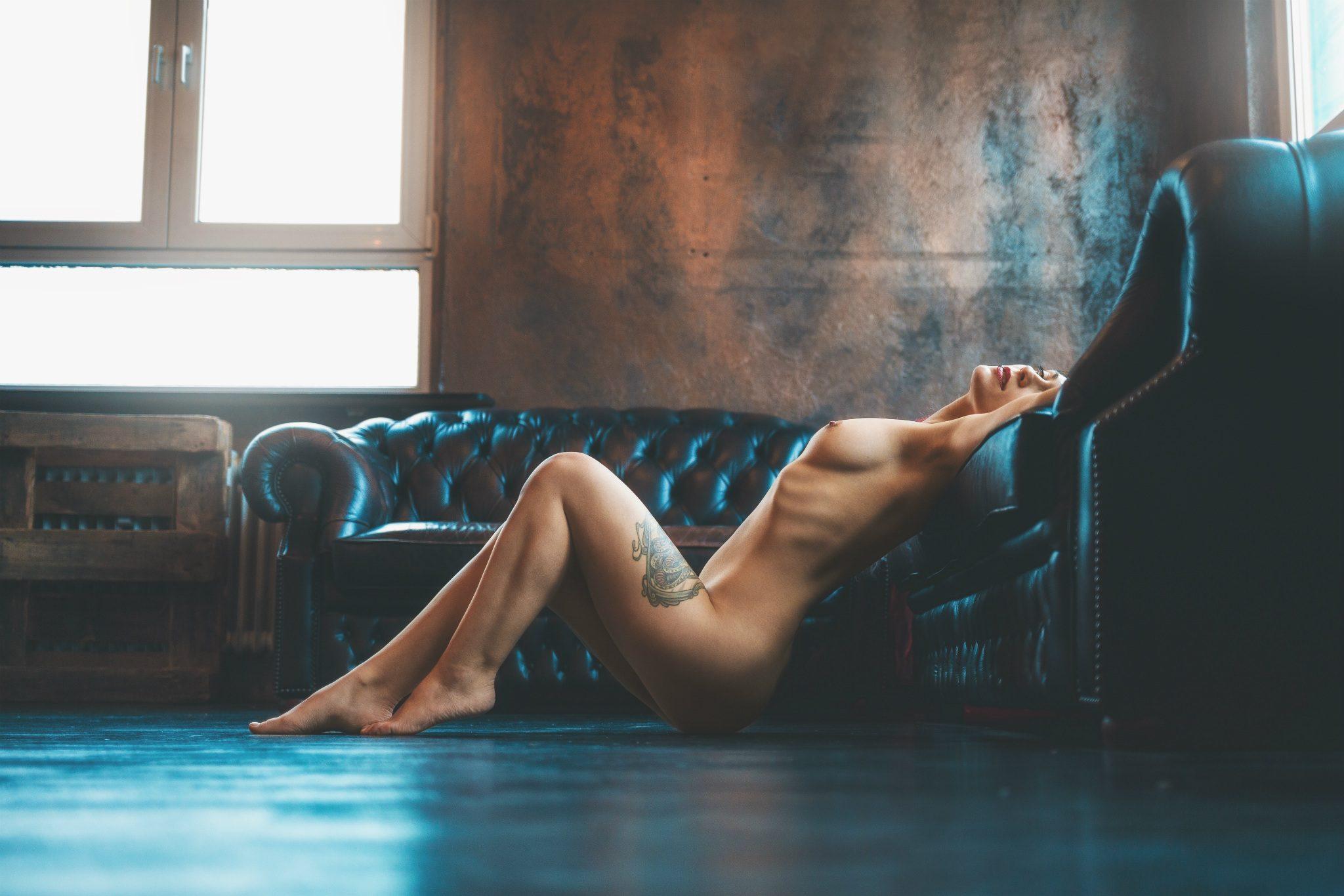 Anastasia liegt vor der Couch im Lyke an Atelier in Frankfurt und lehnt sich an.